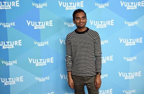 Brown man in black- and white-striped shirt and grey pants stands in front of light blue wall with white text