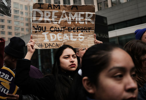 """A young Brown woman holds up a sign that says """"I am a Dreamer. You can't deport ideals"""" at a New York City protest"""