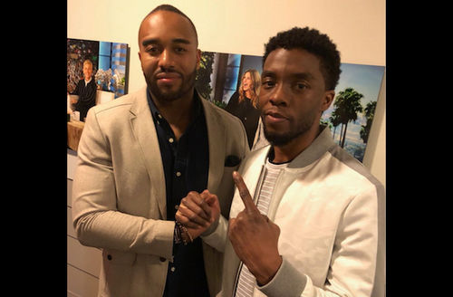 Black man in brown blazer and navy shirt holds hand of Black man in white jacket and grey shirt with white stripes in front of blue and green images and brown wall