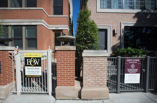 Two brick homes next to each other with for sale signs on their front gates