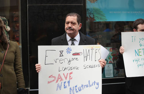 Brown man in grey suit and tie holds white poster with blue and red and black text and logos in front of black storefront with blue sign