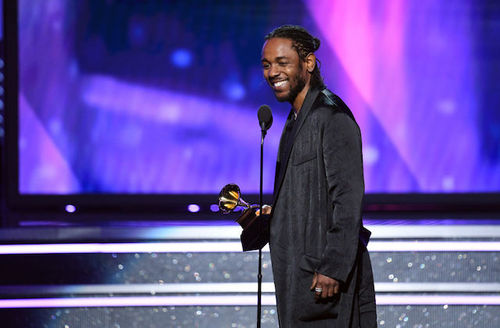 Black man in black jacket and shirt holding gold awards statue behind black microphone and stand in front of purple background
