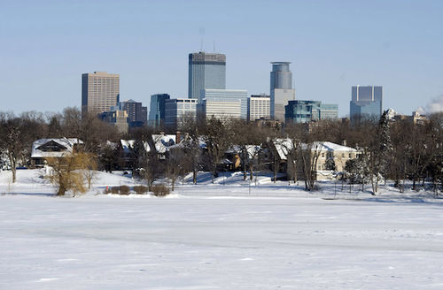 White snow over frozen lake in front of brown houses and grey and blue city skyline and blue sky