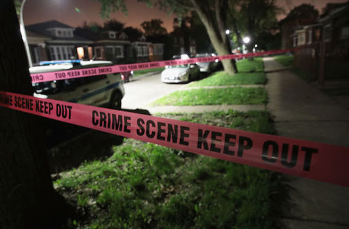 Red and black crime scene tape stretched in front of a home