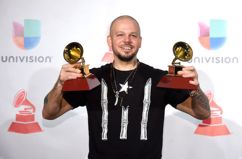 Brown man in black t-shirt with white star and stripes holds two gold awards statues with red bases in front of white wall with multicolored insignia and black text