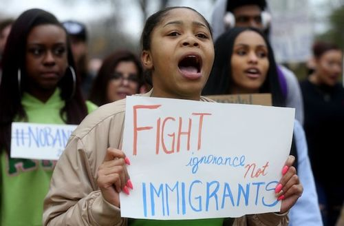 "A Black woman with a sign that says ""Fight ignorance not immigrants"""