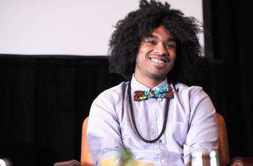 Black man with black afro in light purple shirt and black lanyard and black and blue and yellow and red bowtie sits on orange chair in front of black curtain and grey screen