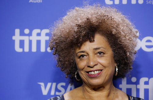 Black woman with brown afro and gold earrings in blue shirt smiles in front of blue background with grey text
