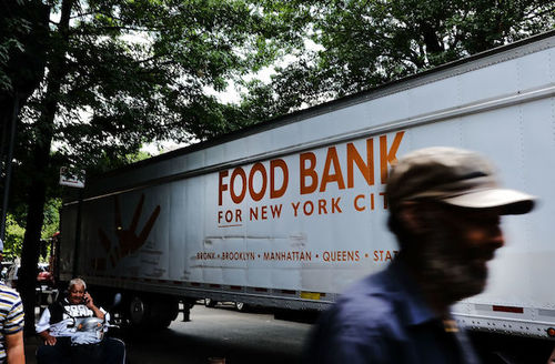"White semi truck with orange lettering that reads, ""New York Food Bank"" on city street"