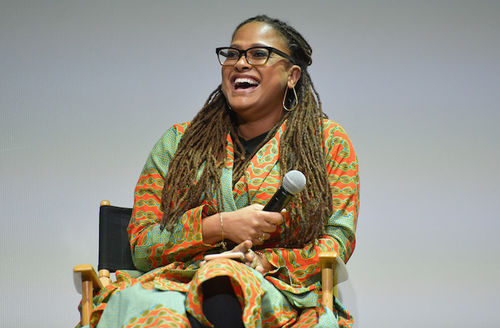 Black woman with brown dreadlocks wears black glasses and green and orange dress while smiling and holding black microphone and sitting in black and brown directors' chair in front of grey wall