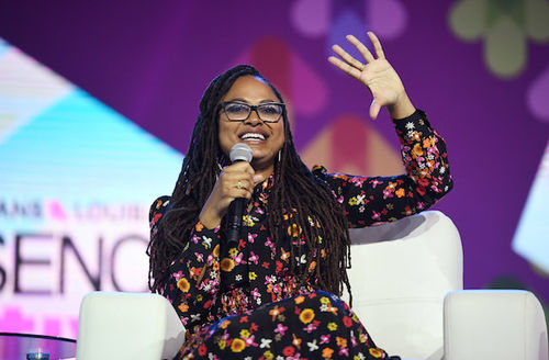 Black woman in black dress with pink and yellow flowers and black glasses smiles and raises hand while holding black microphone and sitting in white chair in front of purple and pink background