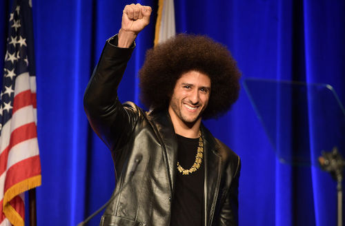 Black man with black afro in black leather jacket and shirt and brown necklace raises fist and smiles in front of blue curtain and red and white and blue U.S. flag
