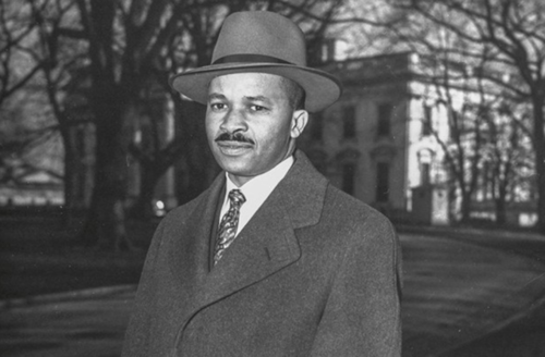 Black-and-white photo of black man in fedora and overcoat and tie on white shirt in front of white stone building and grass