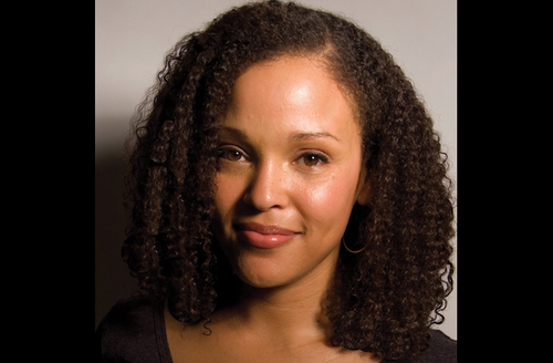 Black woman with brown hair in black shirt in front of grey wall