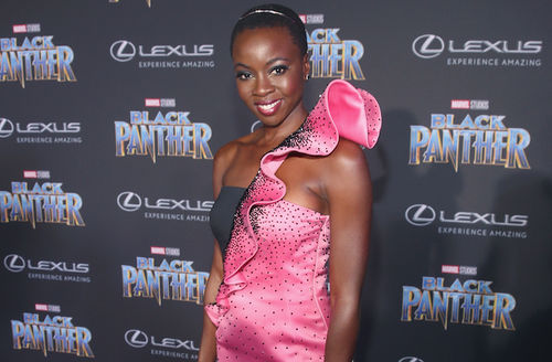 Black woman in pink dress with black blouse in front of dark grey wall with light blue and grey and red and white text and logos