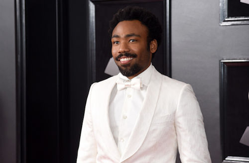 Black man with black hair and moustache smiles in white tuxedo in front of dark grey wall with grey insignia