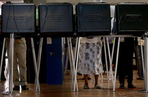 People stand at voting booths, faces covered by black partitions