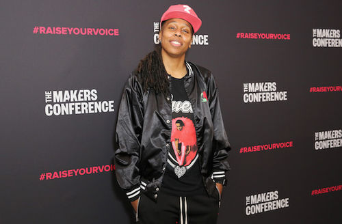 Black woman with black dreadlocks in red baseball cap and black and white jacket and pants and black and red t-shirt smiles and stands in front of dark grey background with white and red text