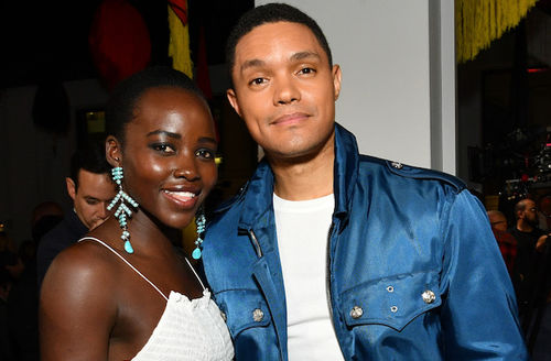 Black woman in white tank top and blue earrings smiles next to Black man in blue jacket and white t-shirt in front of white column and red and yellow curtains