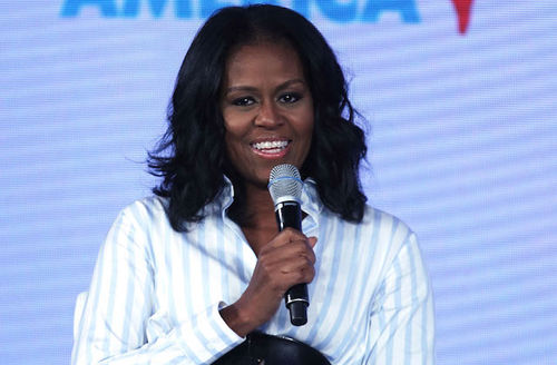 Black woman in white blouse with light blue stripes holds black microphone and smiles in front of light grey screen with light blue text and red insignia