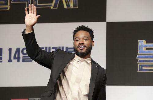 Black man with black hair in black suit jacket with White shirt waves and smiles in front of black and white wall with blue and red and white text