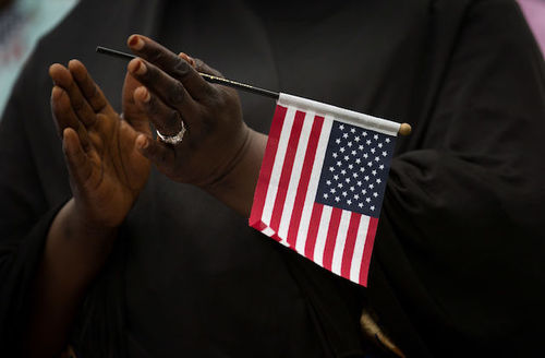 Black hands holding a small, red, white and blue flag.