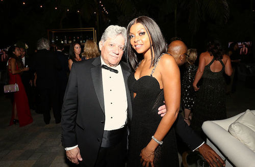 White man in black tuxedo stands next to Black woman in black dress in front of people in red and black and white clothing and darkly lit wall and bar