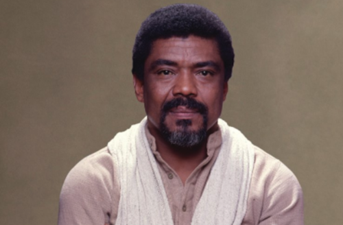 Black man in white scarf and beige shirt in front of light brown background
