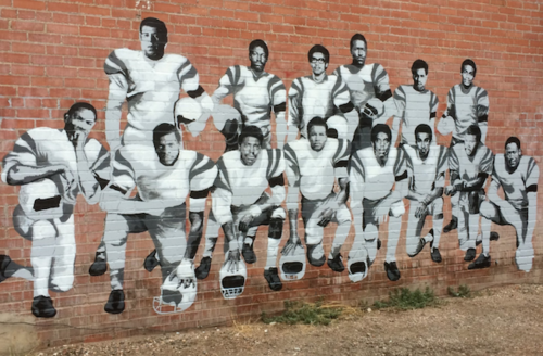 Black-and-white mural depicting 14 black men in grey and black football uniforms on red brick wall