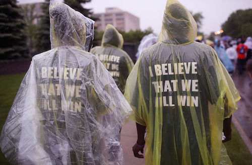 "Protesters in clean rain ponchos. Shirts say, ""I believe that we will win."""