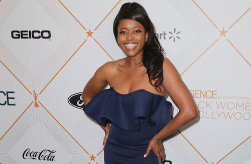 Black woman with black hair and dark blue dress smiles in front of light grey wall with orange detail and grey text and black logos