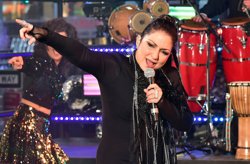 Brown woman in black dress and scarf holds black microphone on black stand in front of dancer in black and gold attire and red and brown percussion instruments and blue lights