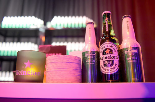 Green and grey beer bottles and candle with white labels sig next to stack of white and green beer coasters in front of black wall and shelves with green and grey bottles