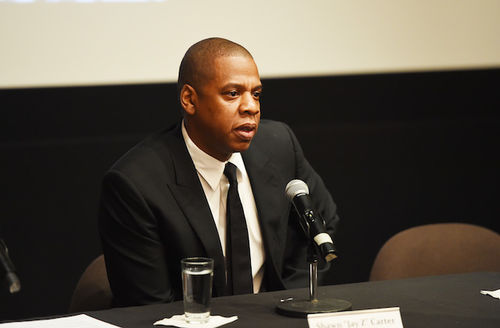 Black man in black suit sits at black table with black microphone white napkin and nameplate with black text in front of black wall with brown screen