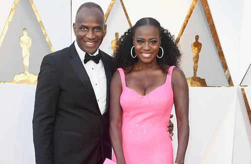 Black man in black and white tuxedo smiles next to Black woman in pink dress in front of white wall with gold ornamentation and insignia