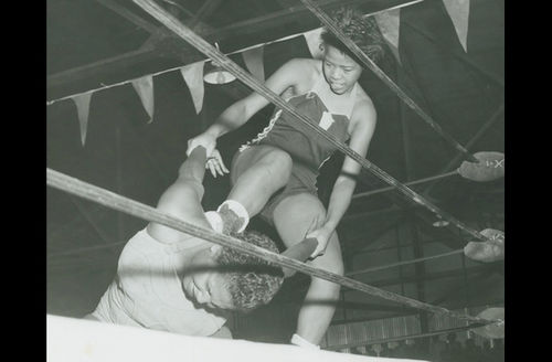 Black-and-white photograph of Black woman in black outfit standing over Black woman in white outfit behind white wrestling ring ropes and in front of dark background