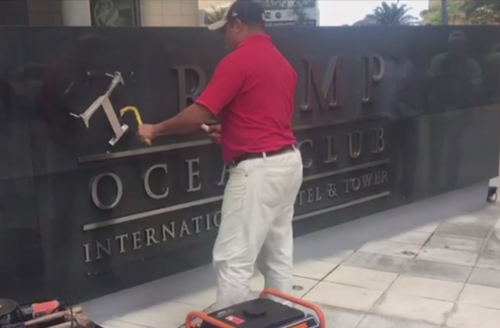 Man in red shirt and tan pants uses crowbar to remove Trump name from sign.