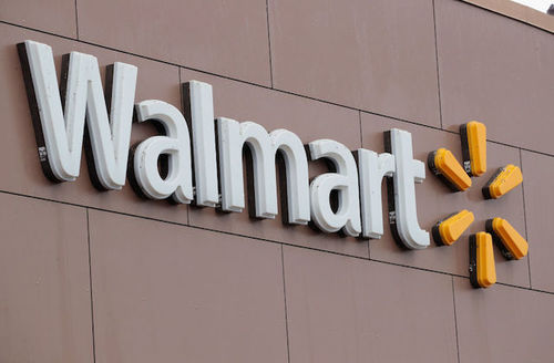 walmart store sign white font on beige concrete with a yellow asterik