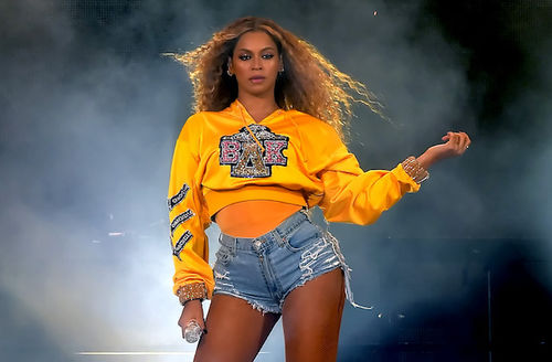 Black woman with blonde hair in gold windbreaker with black and pink and gold and silver logos and embroidery and yellow shirt and blue denim shorts holds grey microphone in font of black background with grey smoke and white light