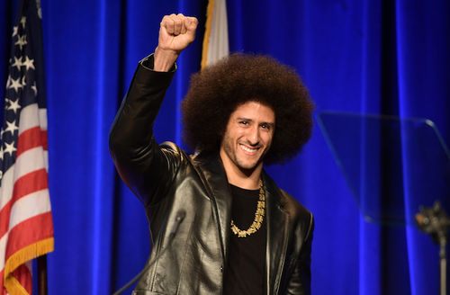 Black man with black afro and beard in black leather blazer and t-shirt and brown necklace raises fist in front of blue curtain and red and white and blue U.S. flag