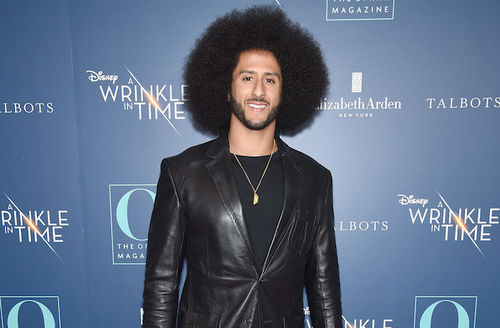 Black man with black afro and beard in black leather suit and shirt in front of blue wall with white and gold and blue text and logos