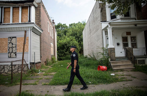 Police officer in uniform walks down street wtih boarded up house.