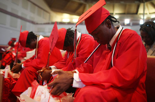 Black boys in red graduation caps and gowns, heads bowed in prayer