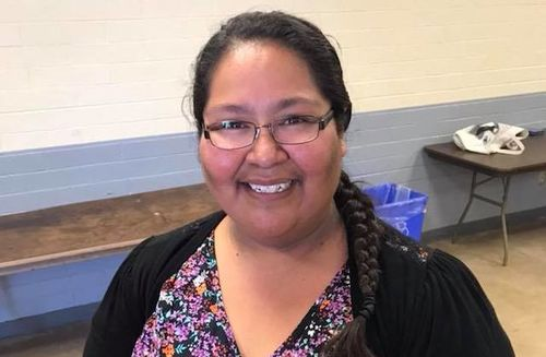 A Native American woman wearing a floral shirt and black sweater smiles