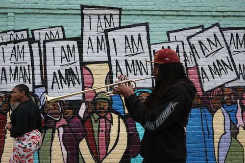 """A Black man wearing a black sweatshirt and red cap over dredlocks and playing a trumpet passes a colorful mural of the Memphis sanitation worker's """"I Am a Man"""" strike"""