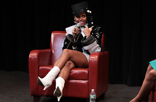 Janelle Monáe. Black woman smiles in black hat and black and white dress and white boots while holding black microphone and sitting on red chair on gray carpet near Black woman in turquoise skirt in front of black wall