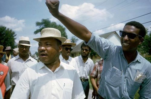 Black man in brown hat and white shirt next to Black man in black sunglasses and blue shirt in front of Black women and men in white shirts and green trees and blue sky