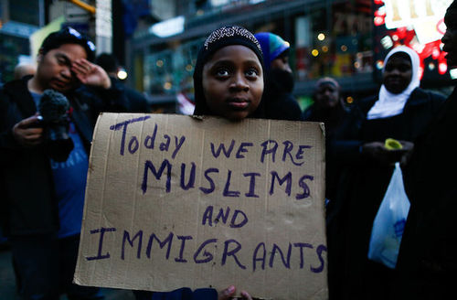 "Brown girl in hijab holds sign that reads, ""Today we are Muslims and immigrants."""