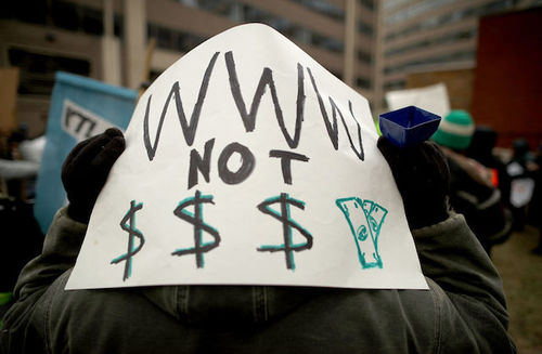 """Someone holds sign on back of their head that reads, """"WWW not $$$"""""""