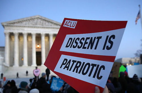 "A hand holds a red and white sign that reads, ""Dissent is patriotic."" The Supreme Court is in the background."